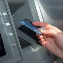 photo of hand holding credit card at ATM